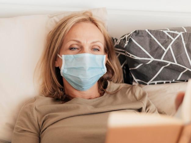 Donna con mascherina medica leggendo il libro in quarantena Foto Gratuite