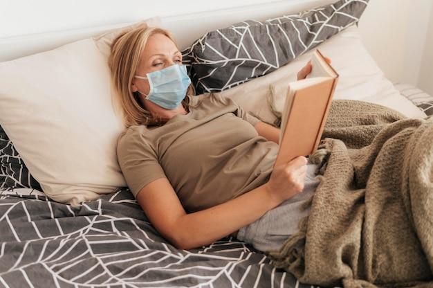 Donna con mascherina medica che legge in quarantena a casa Foto Gratuite