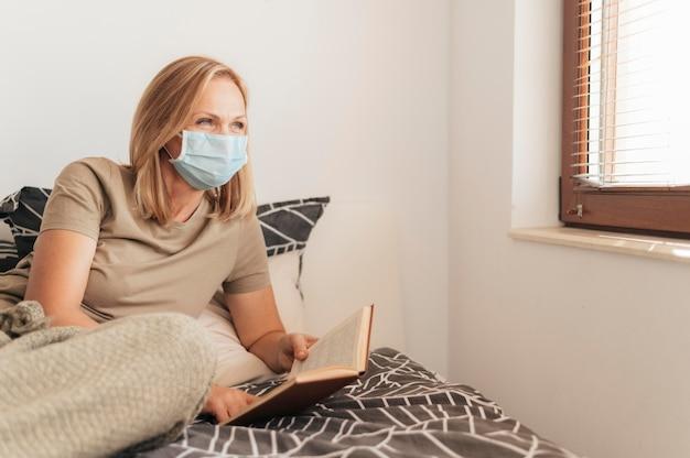 Donna con mascherina medica che legge in quarantena Foto Gratuite