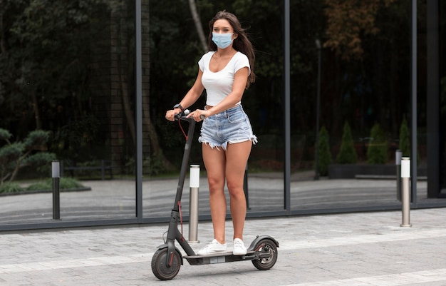 Woman with medical mask riding an electric scooter Free Photo