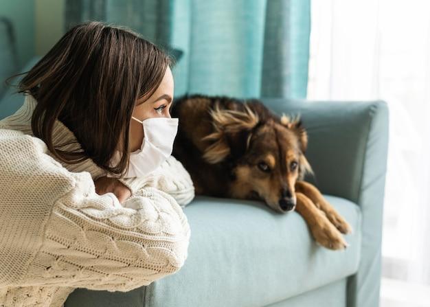 Женщина в медицинской маске сидит рядом со своей собакой дома во время пандемии Бесплатные Фотографии