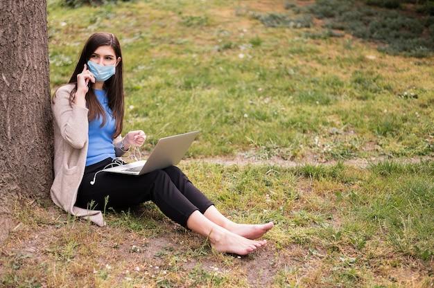 屋外のラップトップに取り組んで医療マスクを持つ女性 無料写真