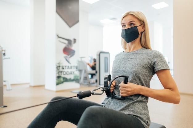 Donna con mascherina medica allenandovi in palestra Foto Gratuite