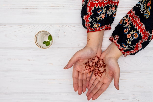 Woman with mehendi on palms near cup with plant twig Free Photo