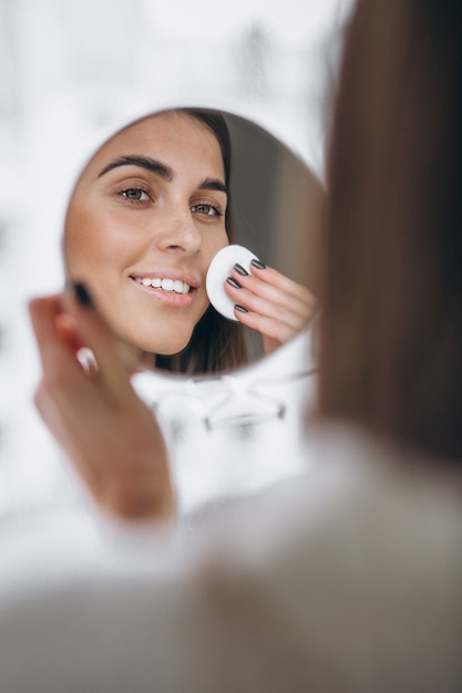 Woman with mirror removing makeup with pad Free Photo