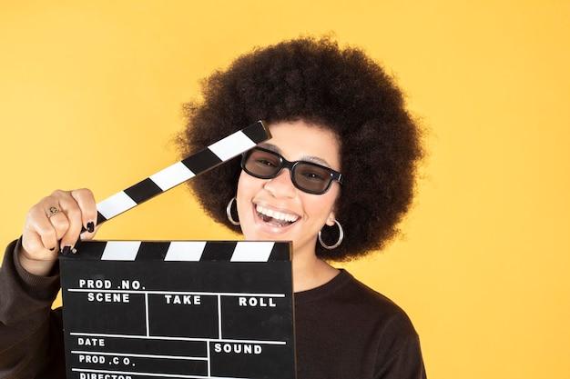 映画のカチンコ黄色の背景を持つ女性 Premium写真