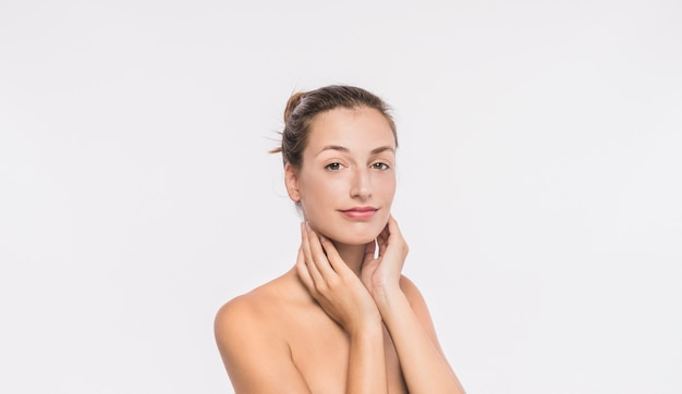 Woman with naked shoulders touching neck Free Photo