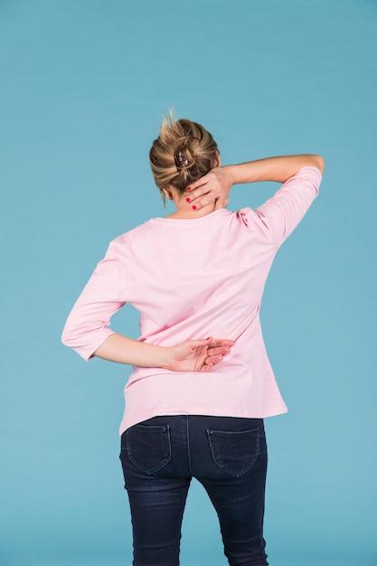 Женщина с шеей и боли в спине, стоя перед синим фоном Premium Фотографии