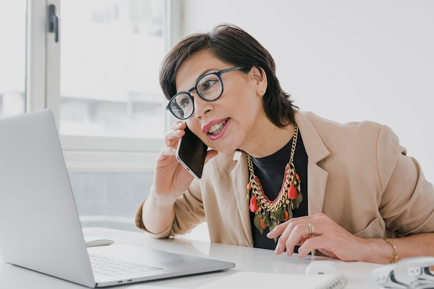 Woman with necklace talking on the phone on her office Free Photo