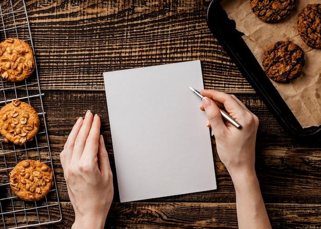 Женщина с бумажным листом и вкусным печеньем на столе Бесплатные Фотографии