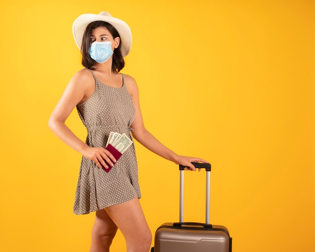 パスポートとスーツケース、マスクを身に着けている女性 Premium写真