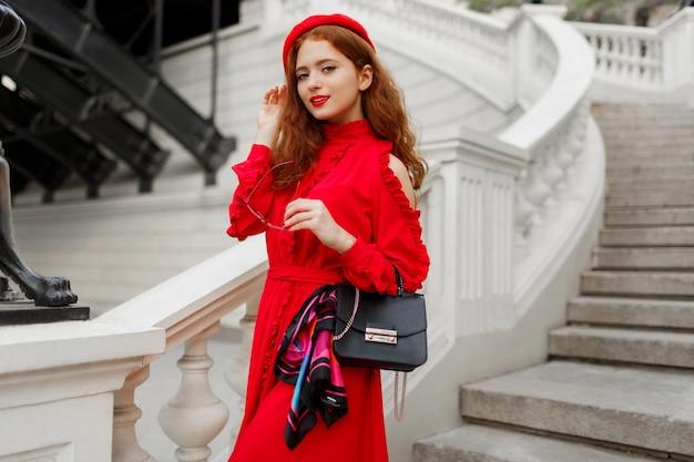 完璧な笑顔、赤い髪、大きな目を持つ女性。赤いベレー帽を着ています。 無料写真