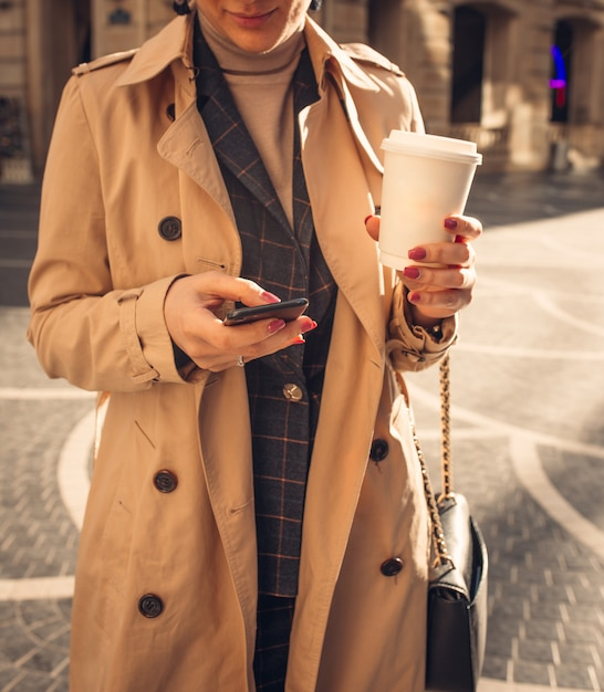 Woman with phone and coffee at fountain square Free Photo