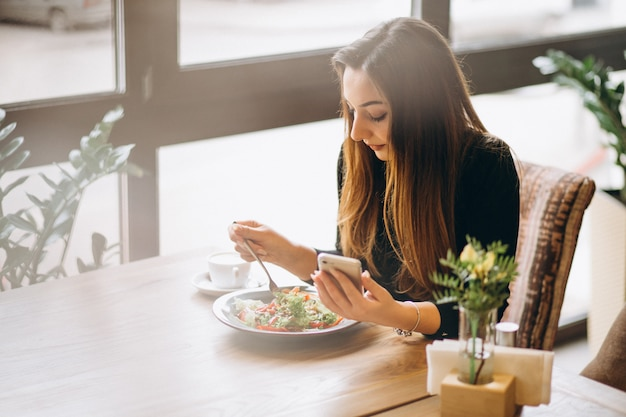 Woman with phone coffee and salad Premium Photo