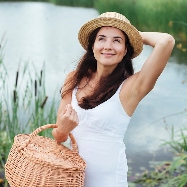 Woman with picnic basket posing by the lake Free Photo