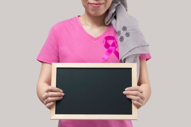 Woman with pink ribbon holding a blackboard. Premium Photo