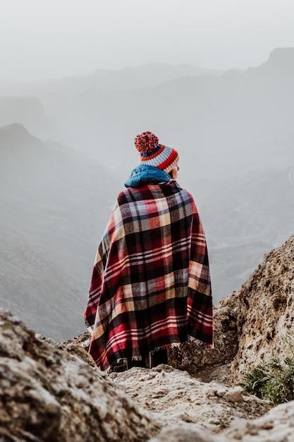 Donna con poncho scozzese e berretto con pompon che si affaccia su uno splendido paesaggio di montagna Foto Gratuite