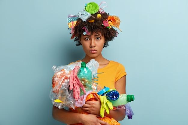 Donna con rifiuti di plastica in borsa a rete Foto Gratuite