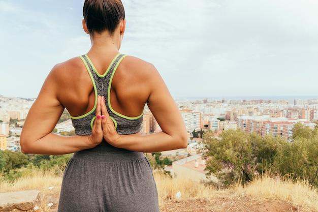 Donna con le mani di preghiera alla schiena Foto Gratuite