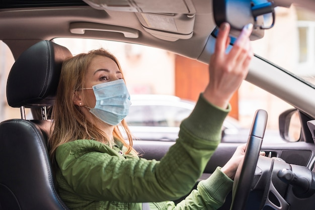 Woman with protection mask in her car Free Photo