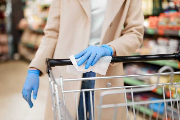 Woman with protective gloves wipes the shopping cart handle with a disinfecting cloth in supermarket. safety during coronavirus pandemic. Premium Photo