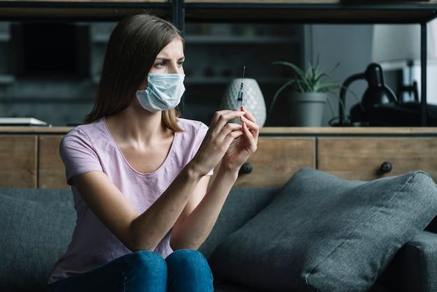 Woman with protective mask sitting on sofa holding syringe Free Photo