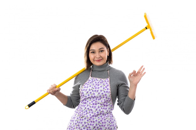 Woman with purple apron and a mop Free Photo