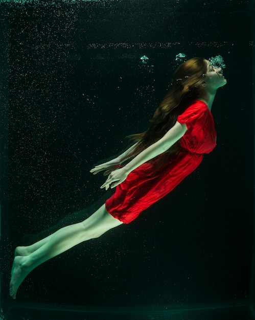 Woman with red dress under water Free Photo