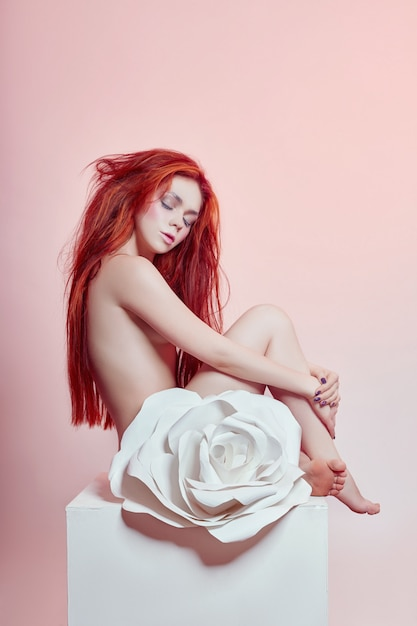 Woman with red hair sitting large paper flower Premium Photo