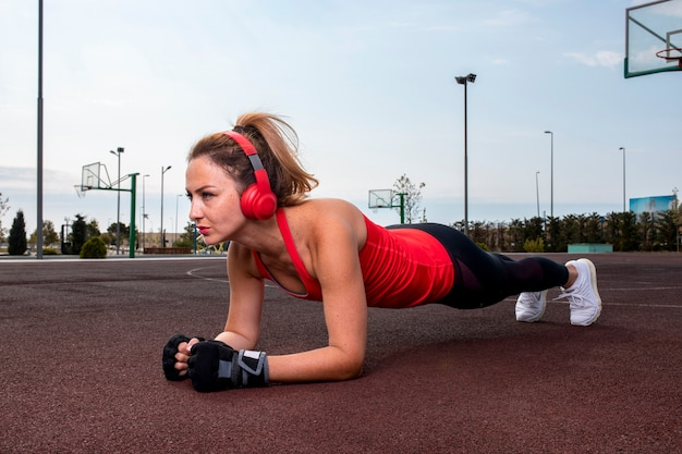 Woman with red headphones doing abs workout on the land in the park. Free Photo