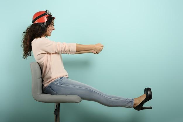 赤いヘルメットをかぶった女性は速い車を運転しようと考えています。シアンの壁。 Premium写真