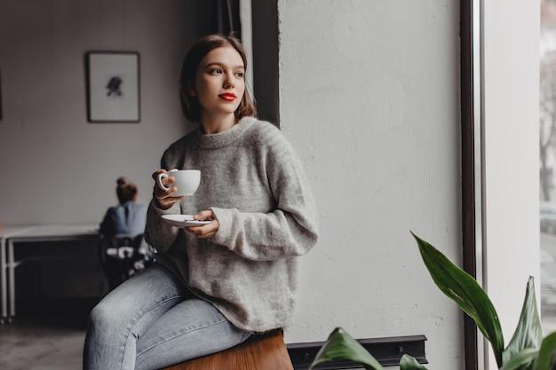 カシミヤセーターに身を包んだ赤い口紅の女性は、オフィスで働く女の子の背景にコーヒーのカップと窓辺に座っています。 無料写真