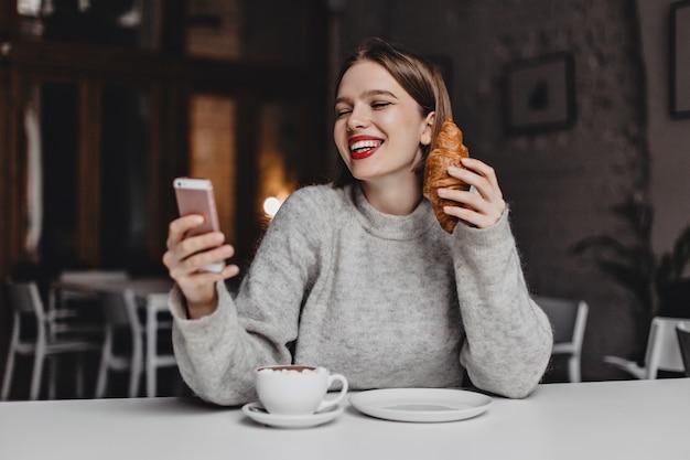 赤い口紅の女性がスマートフォンでチャットしながら笑っています。彼女の手にクロワッサンと灰色のセーターの女性の肖像画。 無料写真