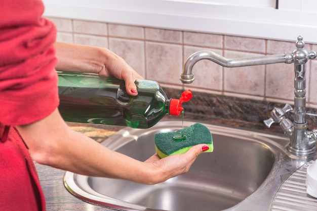 Woman with red manicure putting detergent in the scourer Premium Photo