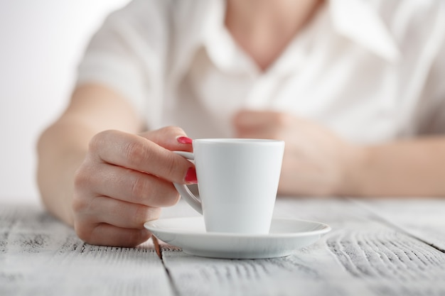 Woman with red nails sitting and holding a hot cup of coffee Premium Photo