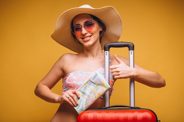 Woman with red suitcase and travelling map in a swimming suit isolated Free Photo