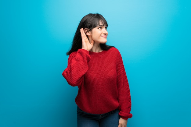 Woman with red sweater over blue wall listening to something by putting hand on the ear Premium Photo