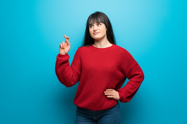 Woman with red sweater over blue wall with fingers crossing and wishing the best Premium Photo