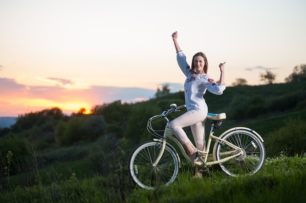 Woman with retro bike standing at hill and showing thumb up at sunset Premium Photo