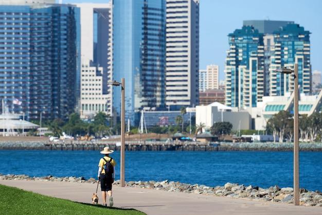 Женщина в круглой классической шляпе гуляет с собакой в парке на набережной в сан-диего Бесплатные Фотографии