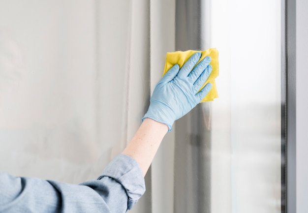 Woman with rubber glove wiping window Free Photo