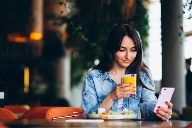 Woman with salad and phone Free Photo