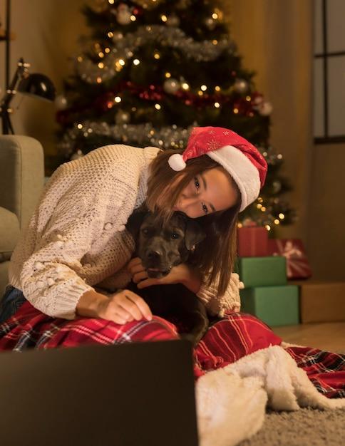 Donna con cappello santa e il suo cane a natale guardando il laptop Foto Gratuite