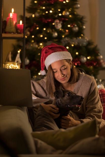 Женщина в шляпе санта держит собаку рядом с ноутбуком Бесплатные Фотографии