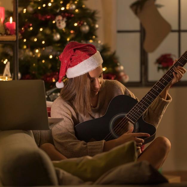 Женщина в шляпе санта играет на гитаре перед ноутбуком Бесплатные Фотографии