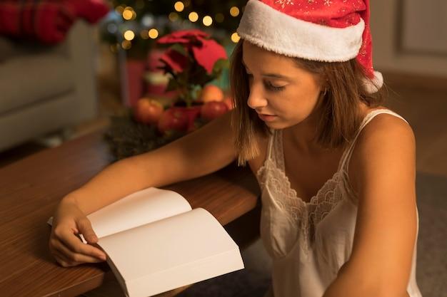 Donna con il cappello della santa che legge un libro sul natale Foto Gratuite