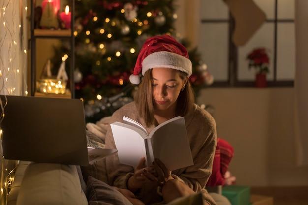 Donna con il libro di lettura del cappello della santa davanti al computer portatile Foto Gratuite