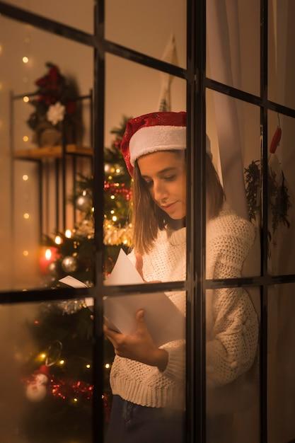 Женщина в шляпе санта-клауса через окно держит и читает книгу на рождество Бесплатные Фотографии