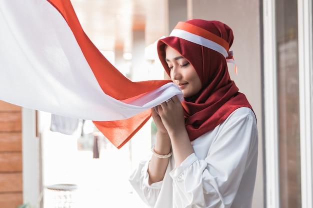 Женщина с шарфом целует флаг индонезии Premium Фотографии