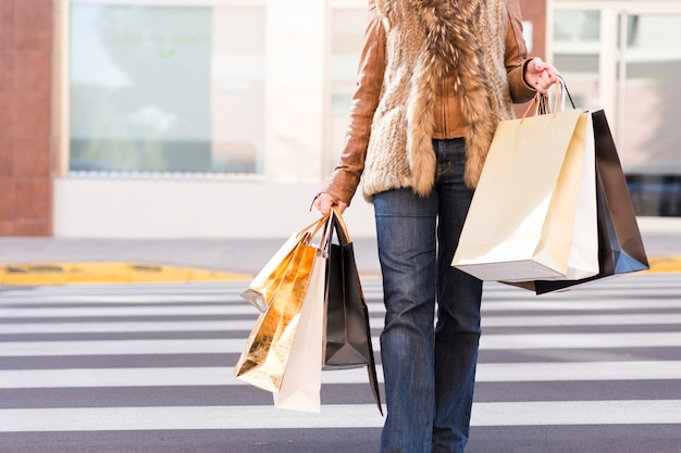 cf6c0d697 Woman with shopping bags on crosswalk Free Photo